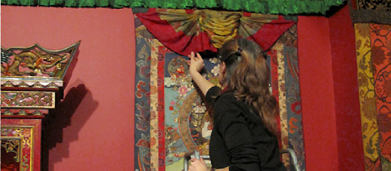 Exhibitions Conservator Jenifer Bosworth arranges drapery folds in thangka installation.