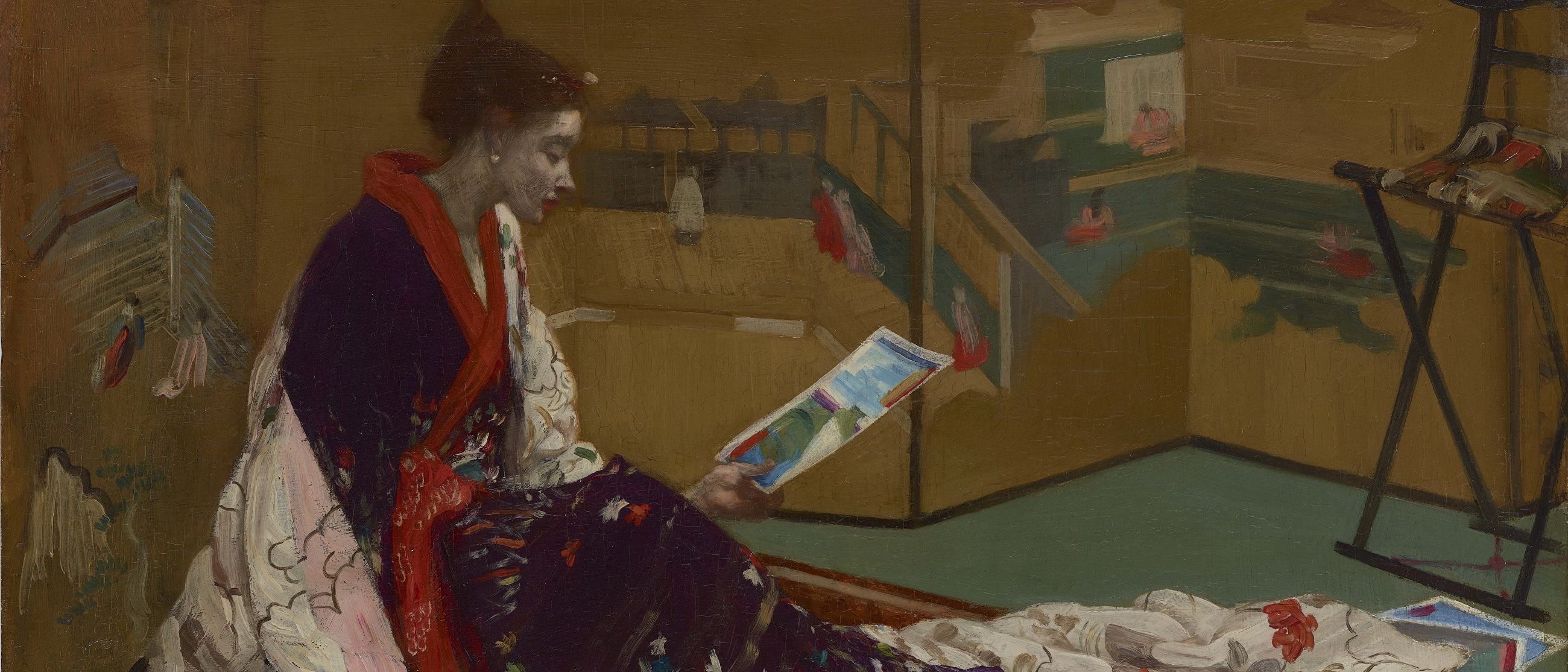 Woman in kimono looking at a leaflet.