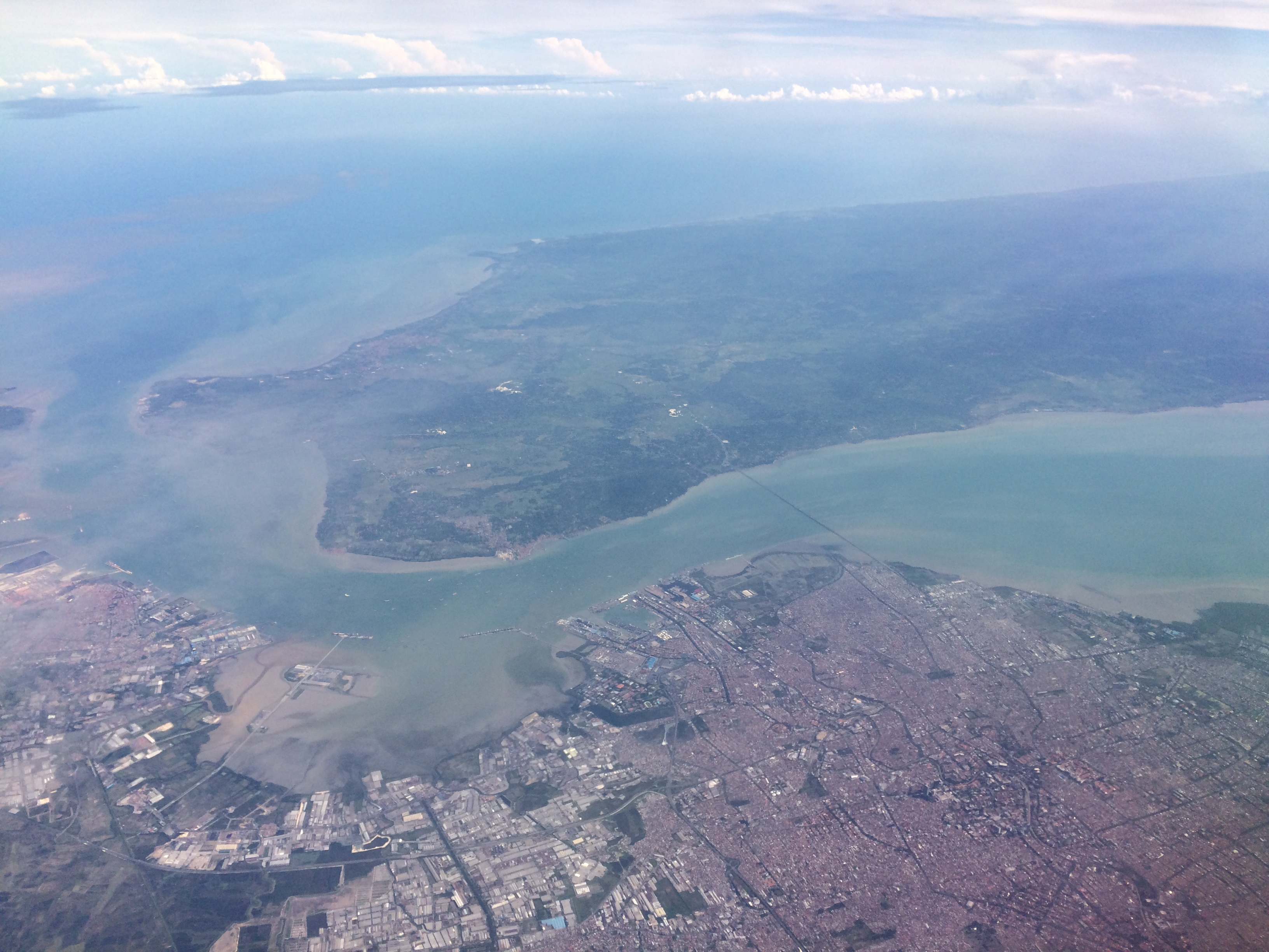 Seen from an airplane, a cityscape with a green island to the north