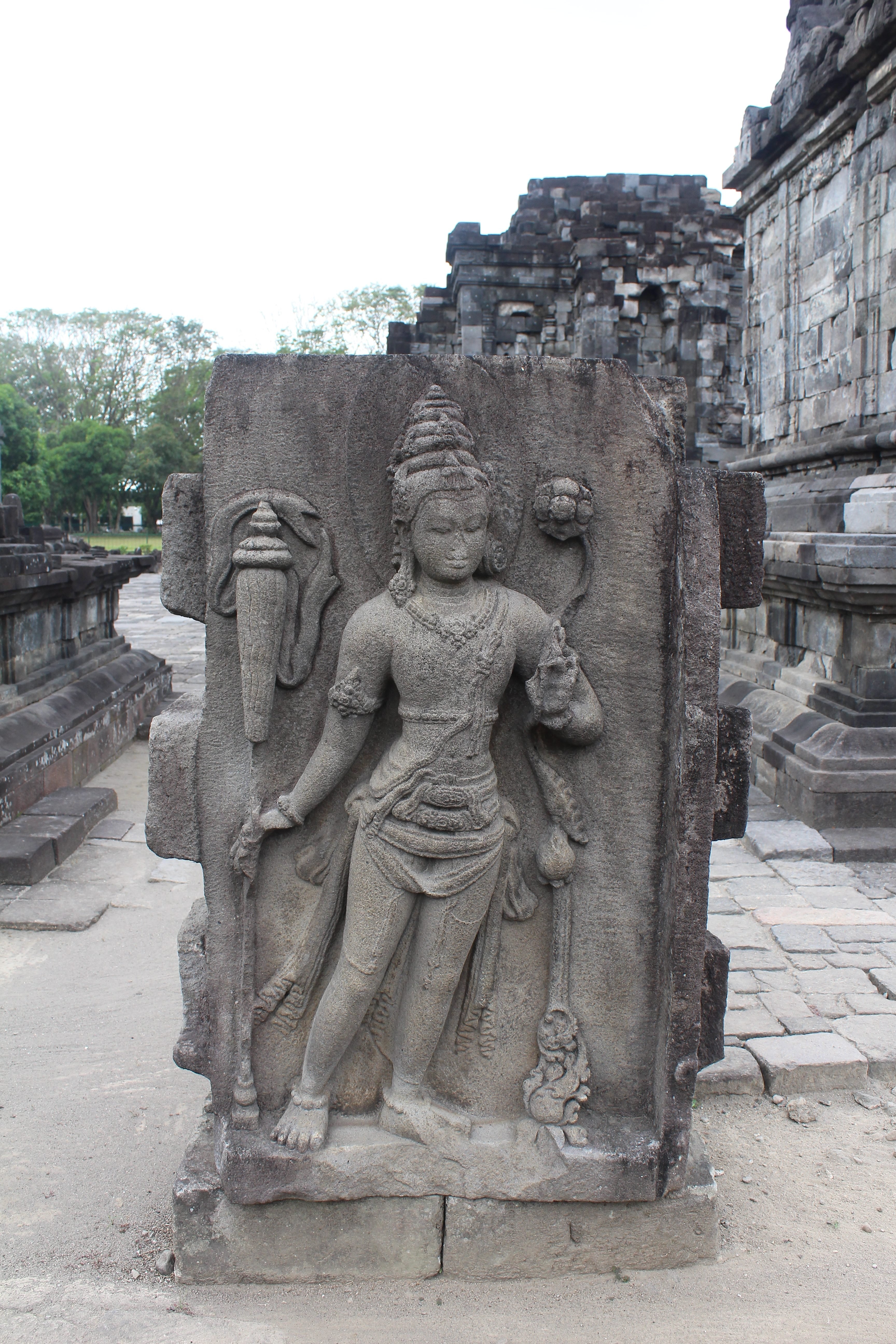 Stone slab with Buddhist figure (Padmapani) carved in relief, in a temple courtyard