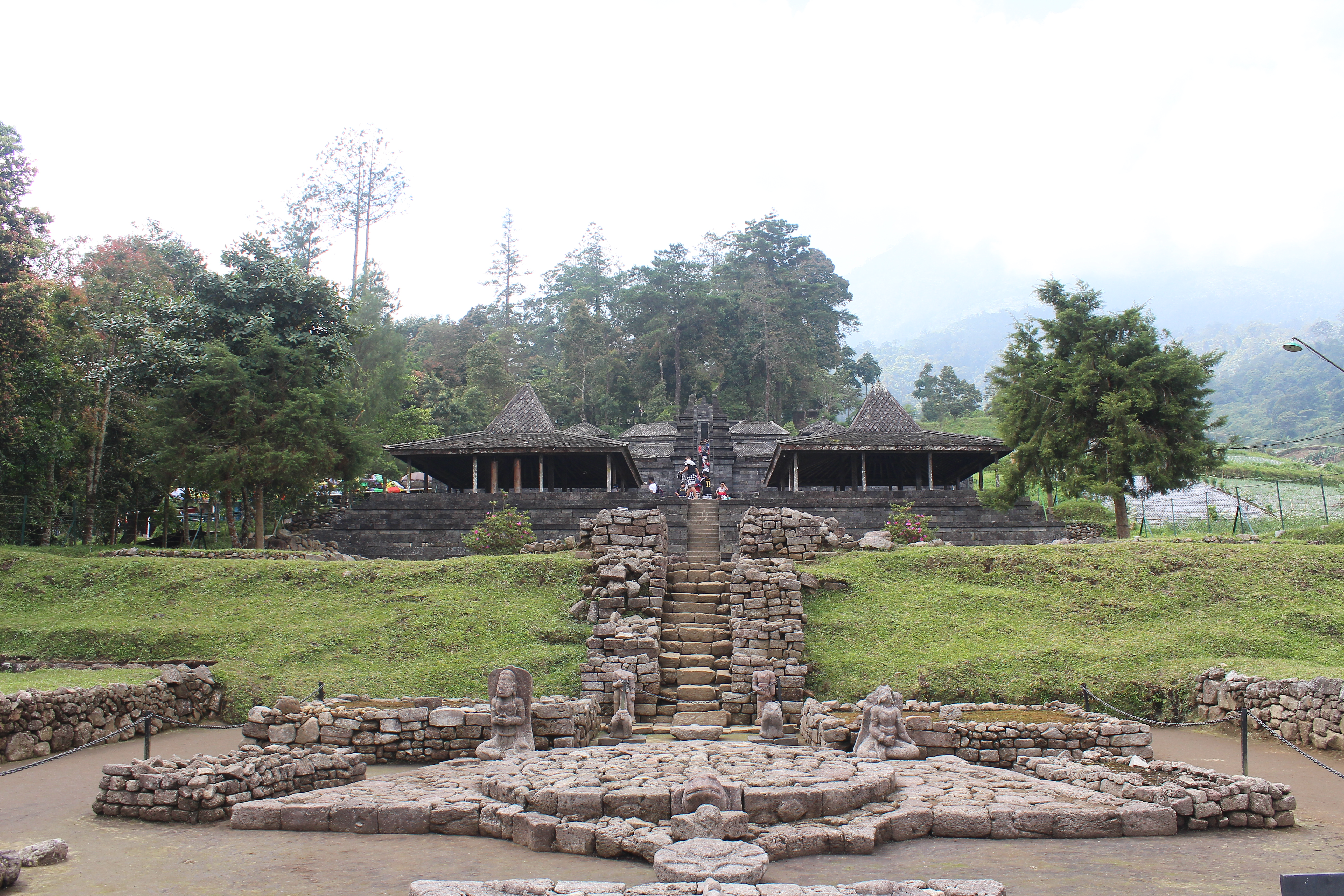 Multi-terraced temple built up the side of a mountain, with stone sculptures in the foreground, a staircase leading up the center, and thatch-roofed hut-shrines above, with tall trees on the mountain higher up