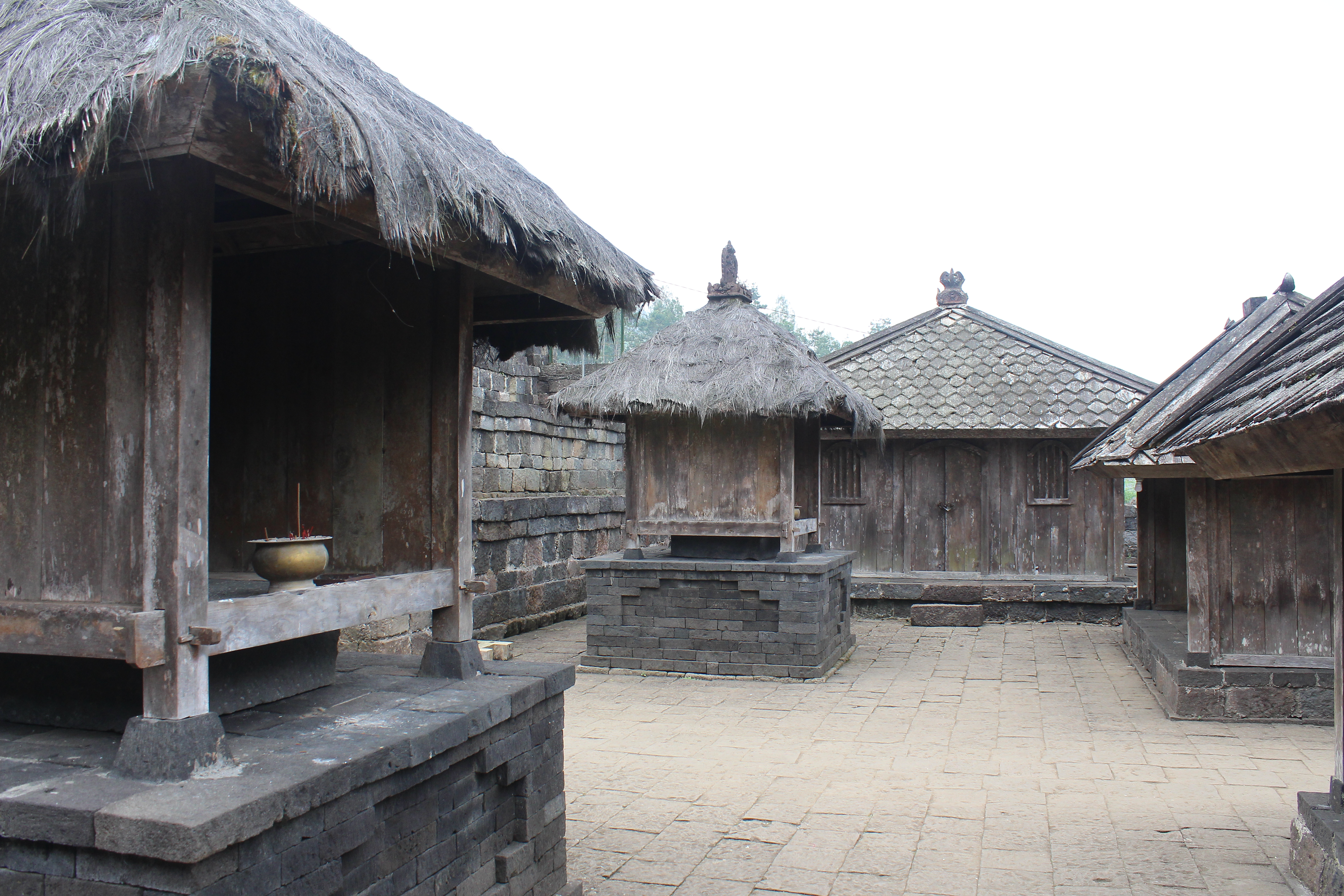 Thatch-roofed shrines and huts with wooden walls