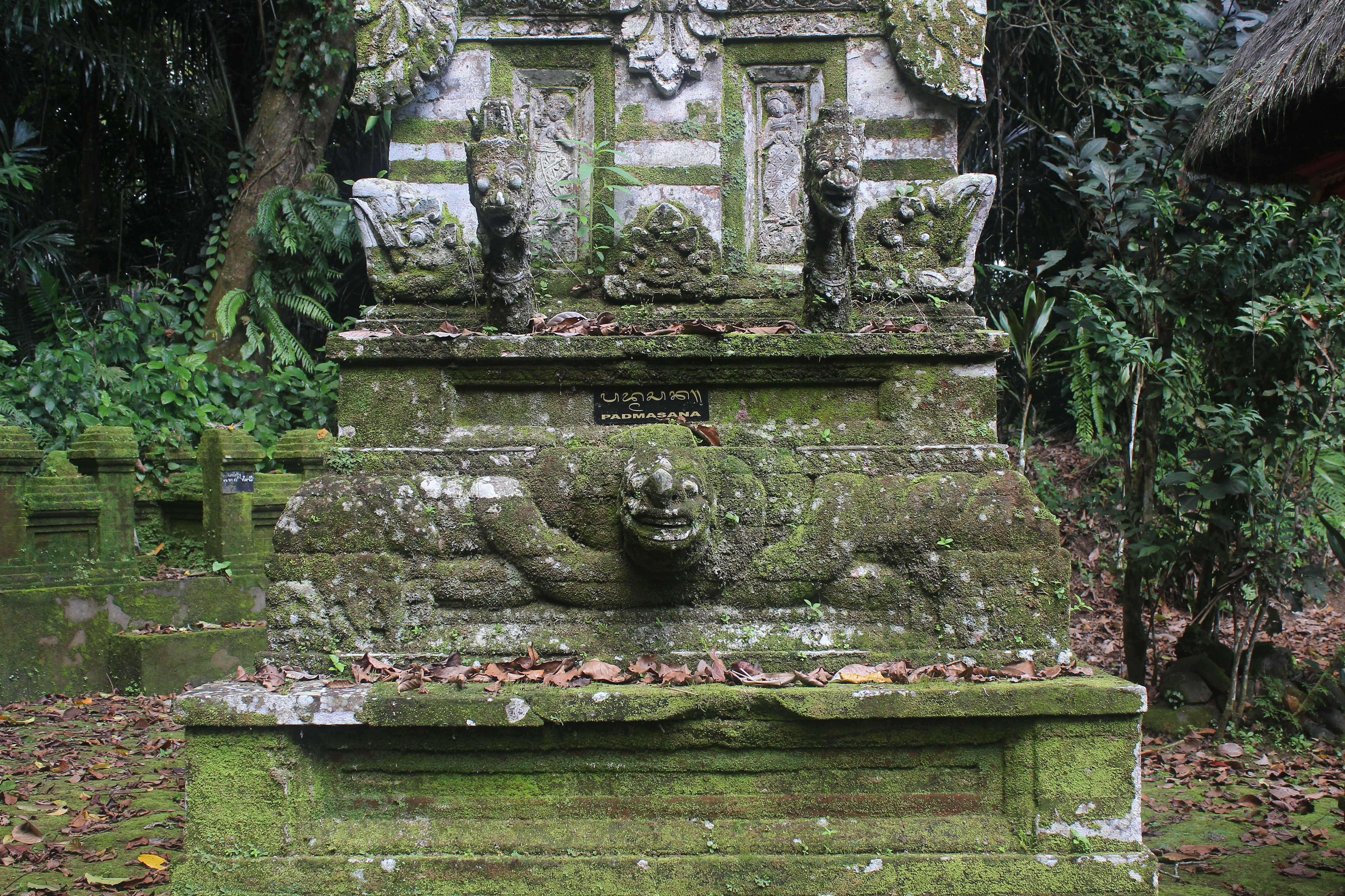 Overgrown shrine with serpent carvings