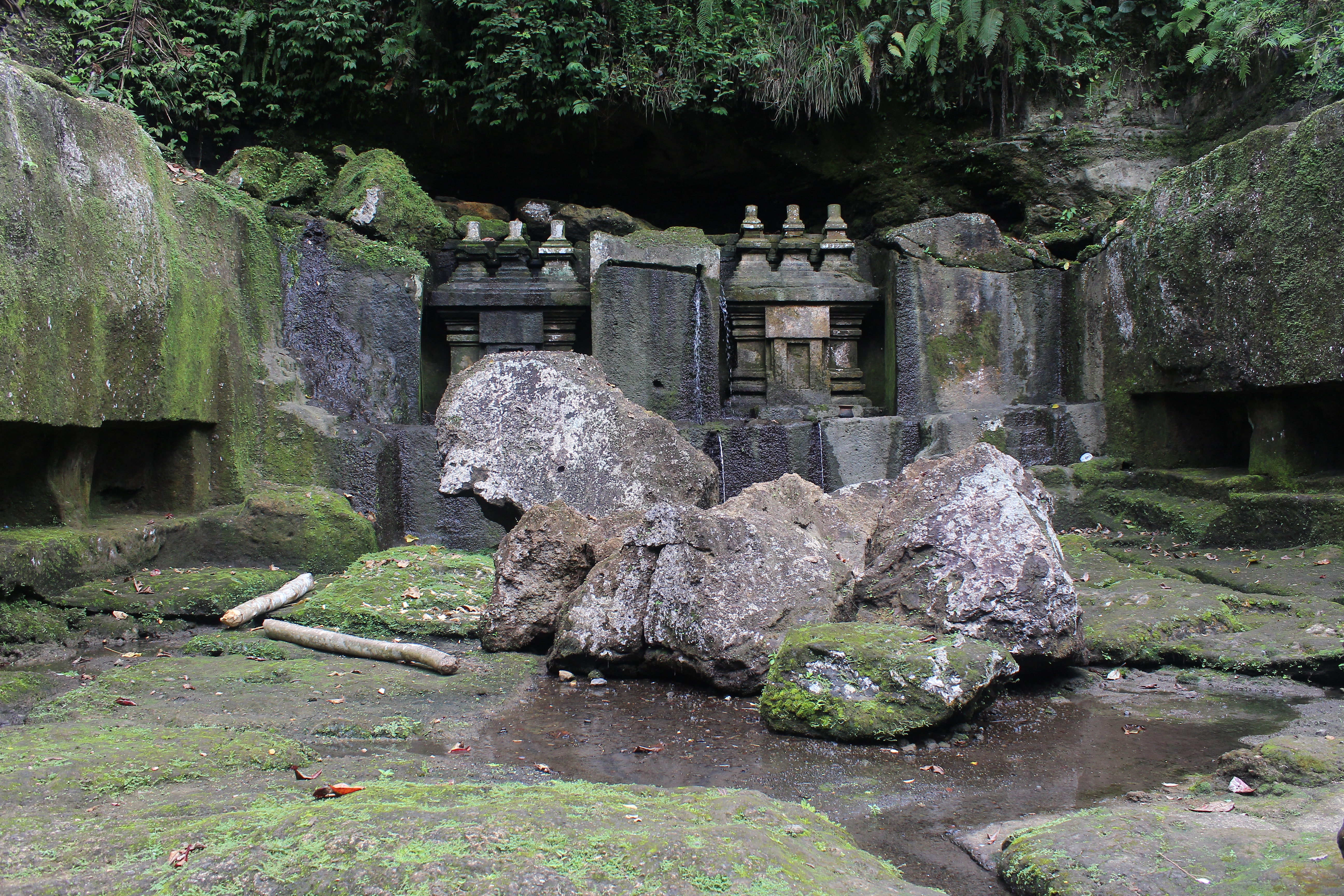 Rock-cut shrine, partially rouined, with caves, a river below