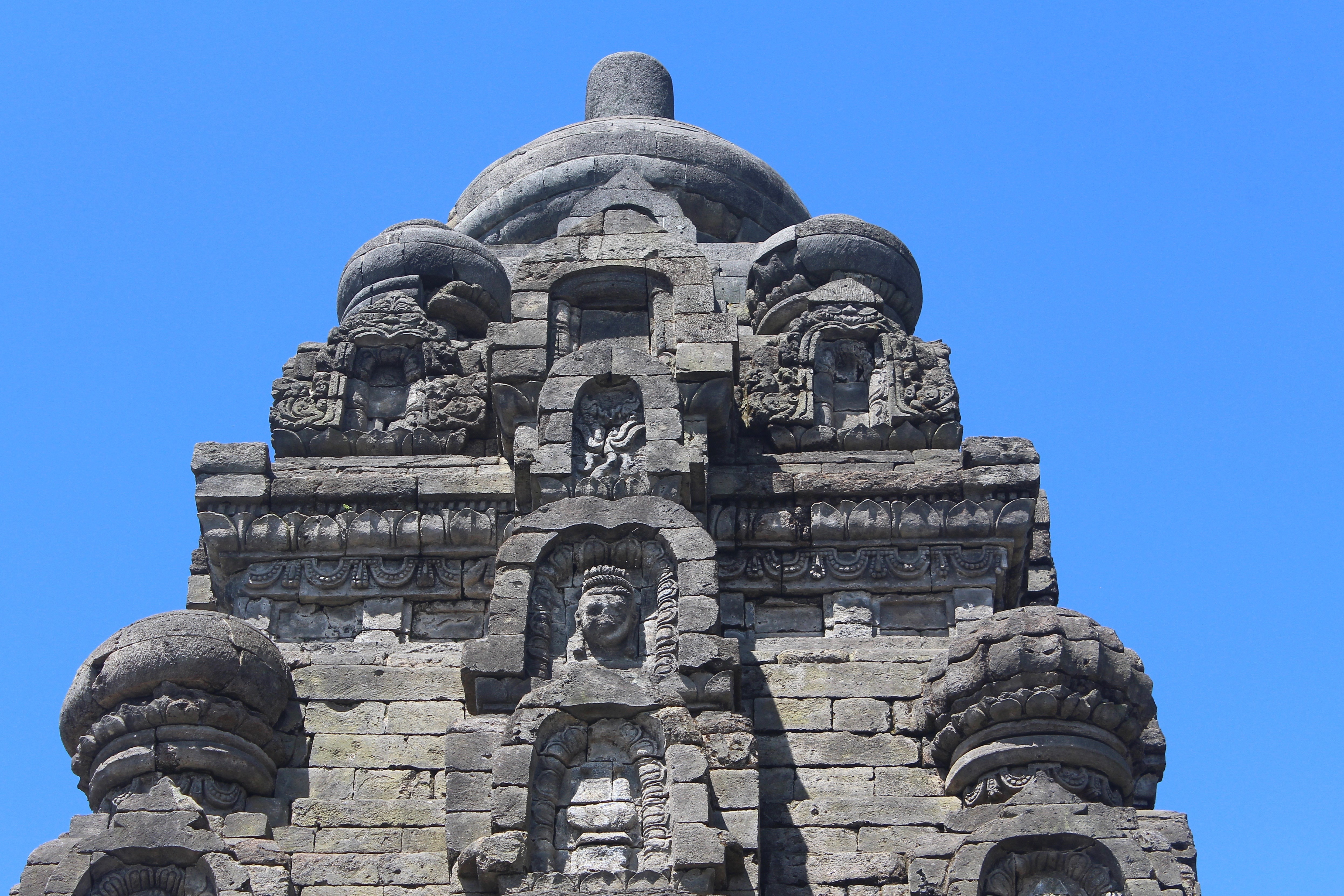 Close-up of stone temple roof with face carved in relief
