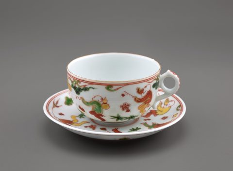 white porcelain cup and saucer with red, green, and yellow designs of children and plants
