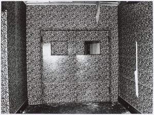 black and white photo of a room wallpapered in busy patterned paper, double doors with windows directly ahead