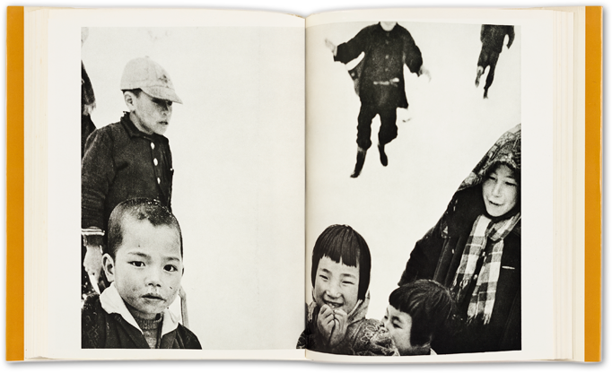 sample spread from Warabegoyomi photobook showing two pages of a book, a black and white photograph across both pages, with several chilren, one laughing, the others looking on