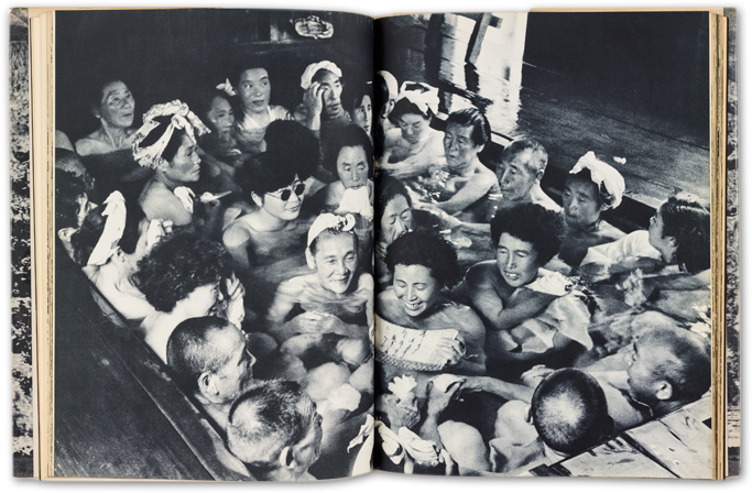sample spread from the Ura Nihon photobook, a black and white photograph across two pages, of a number of people in a bathhouse, crowded into the bath, laughing