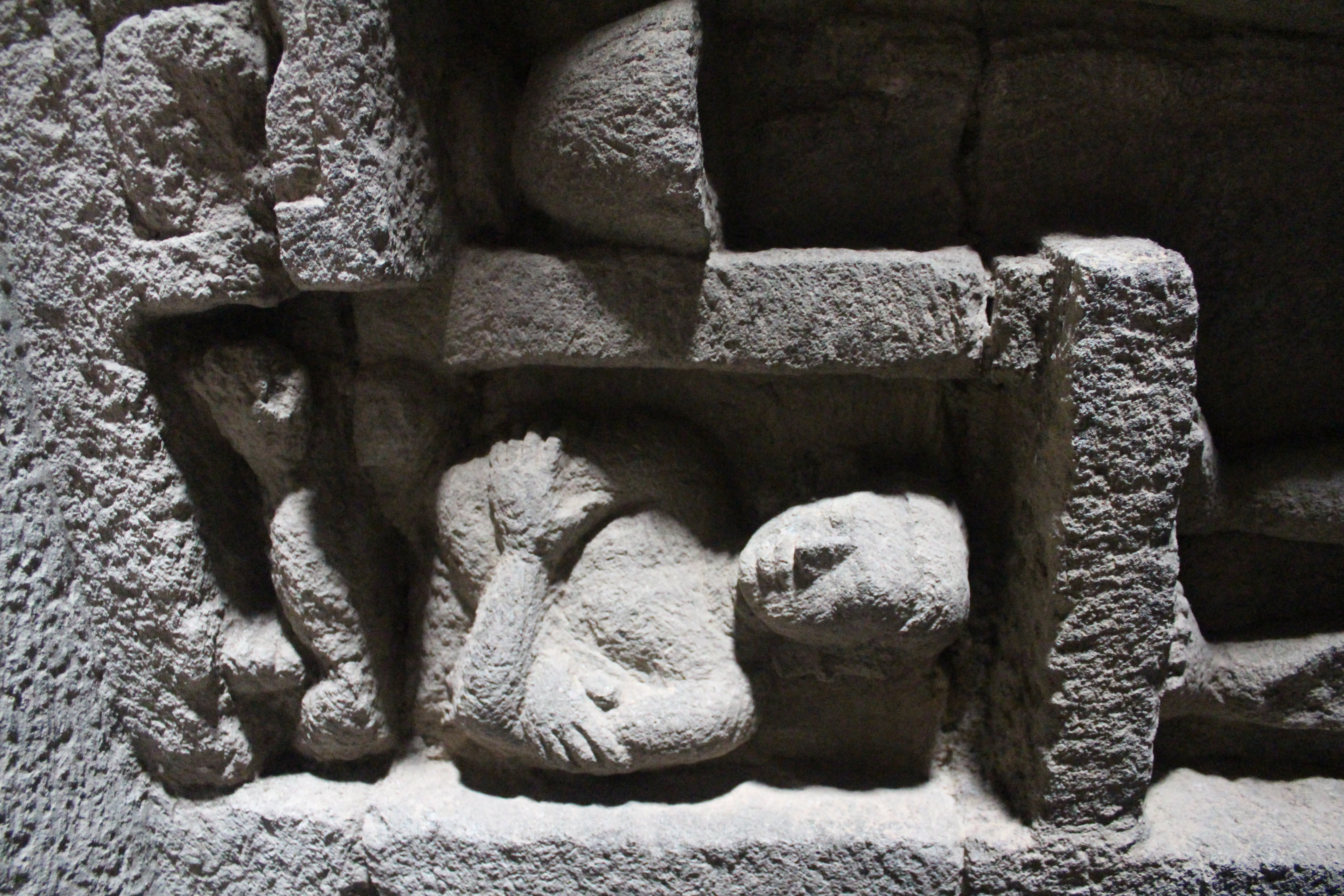 Relief showing a crouching devotee with crossed arms