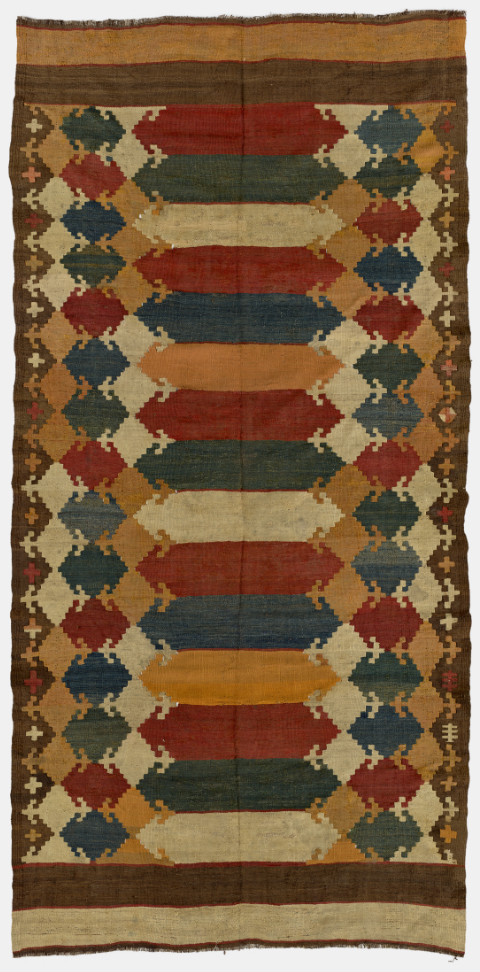 A woven kilim featuring geometric shapes in intense red, orange, dark blue, dark green, white, and black