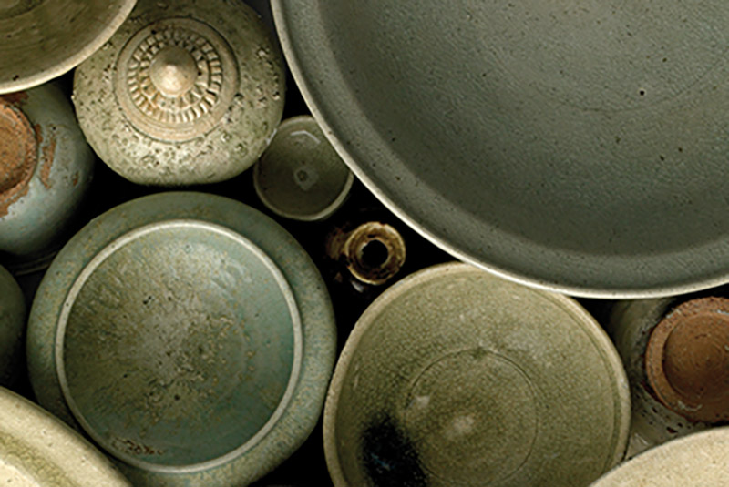 an array of pottery in pale greens and browns, seen from above.