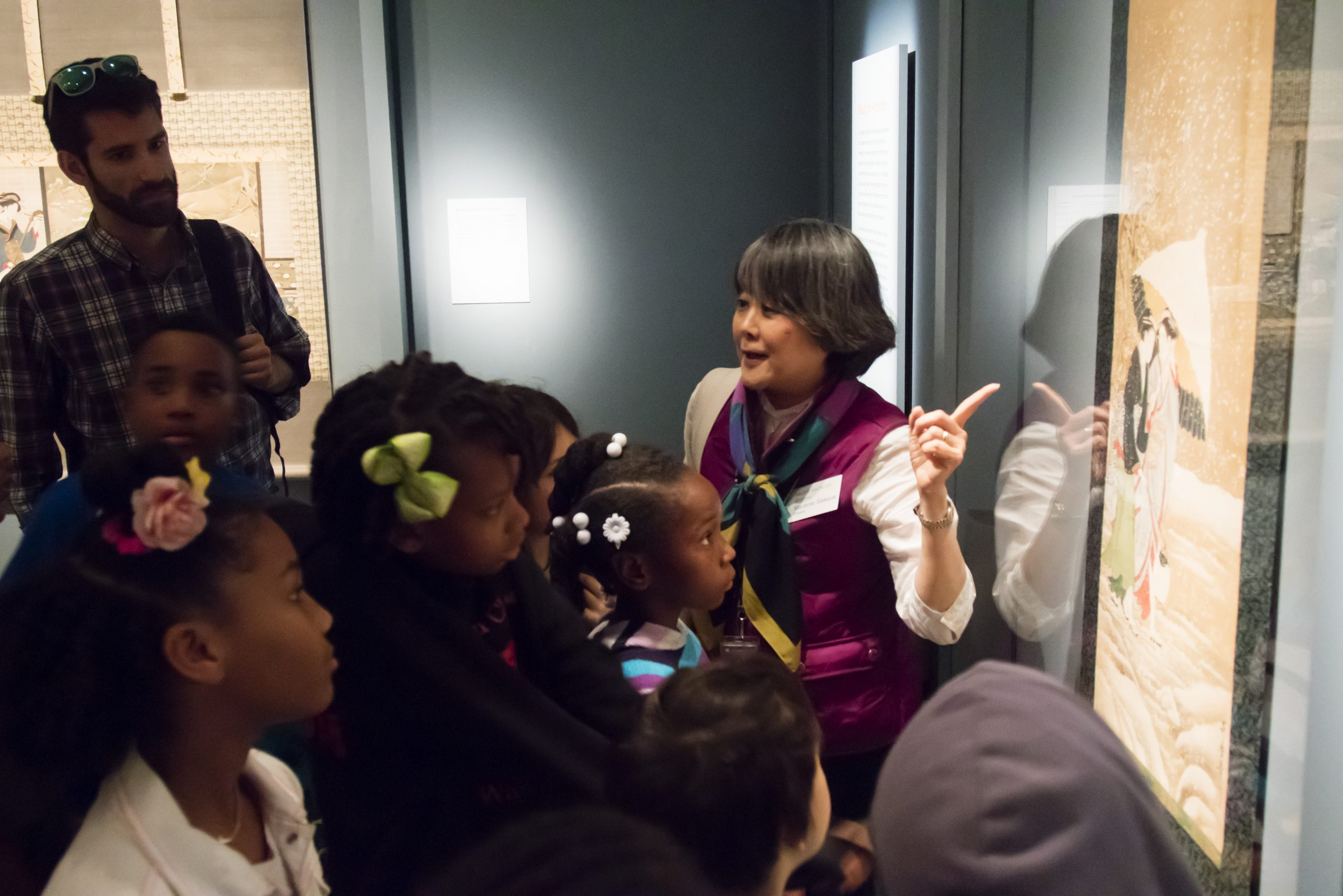 a docent points to artwork in a museum filled with children