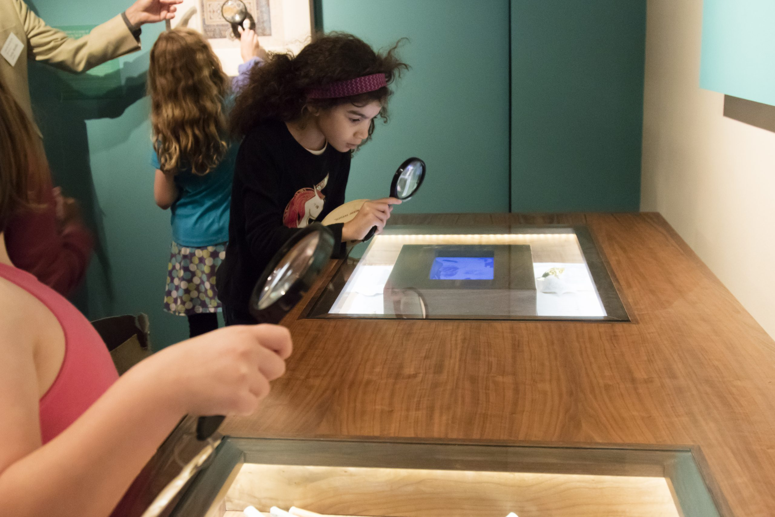 a girl using a magnifying glass over a digital table