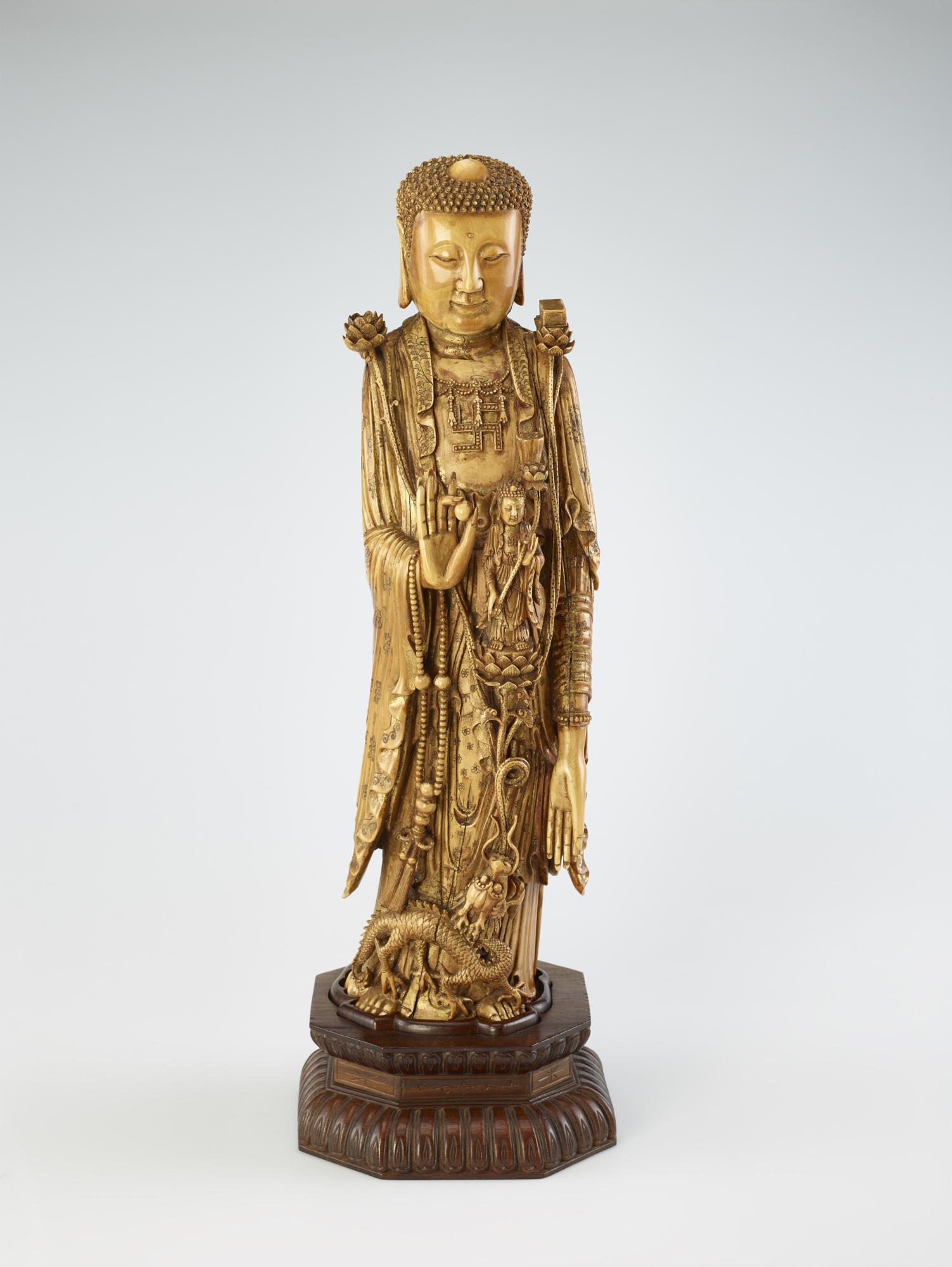 carved statue showing a man holding a seed pod in his hand