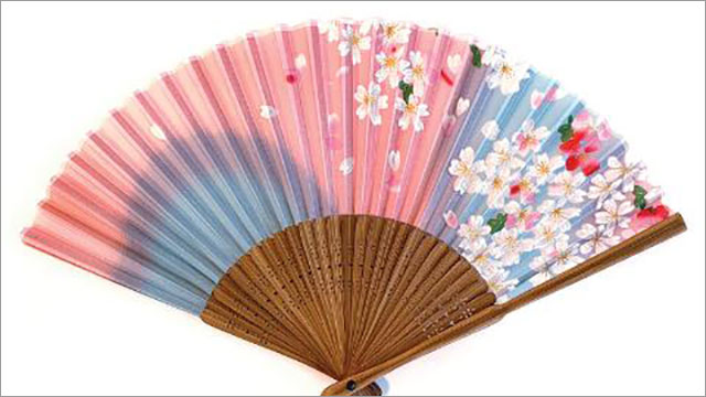 detail of a fan pink and blue decorated with cherry blossoms